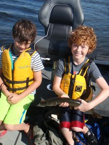 Two young boys holding a net and freshly caught Northern Pike