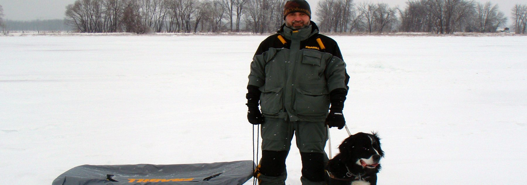 Lawrence and Moby with a sled standing on the frozen ice