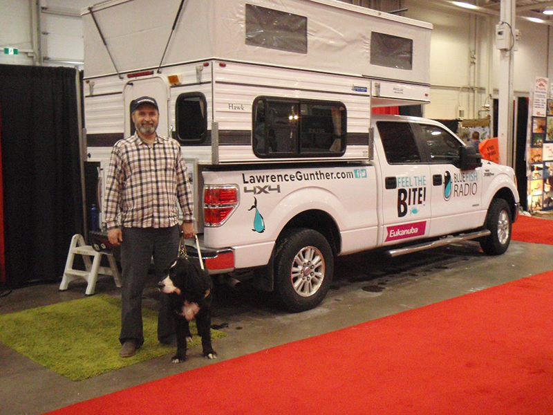 Lawrence with guide dog next to his Ford 150 Camper